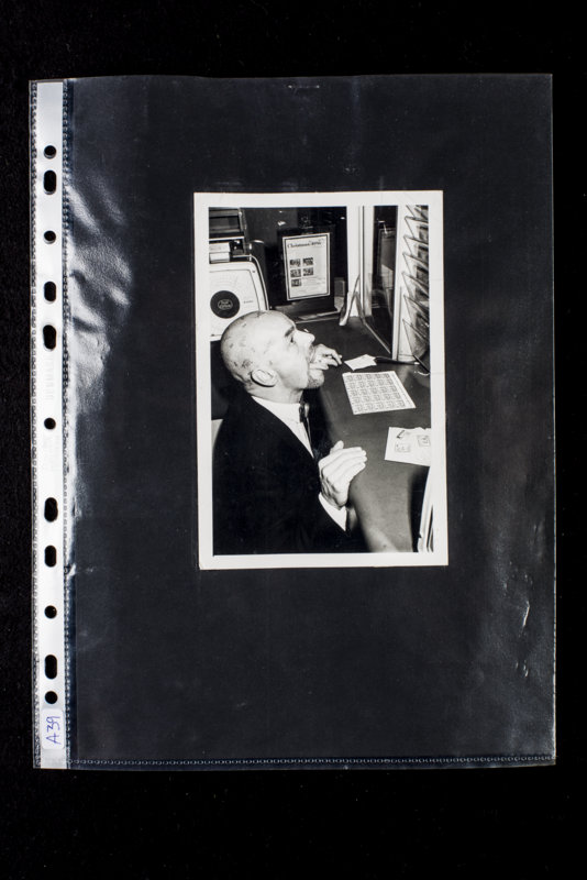 """Edward Voodman's (UK) contribution to """"Send a piece of your nature"""". Envelope with rubberstamps: """"Obsolete Ideology"""", """"Rootine Art Co"""" and """"Post Art Communion 18 november 19$6"""". A photography showing a man kneeling down in front of a desk at a postoffice; on his shaved head rubberstamps and on the tip of his tongue a stamp."""